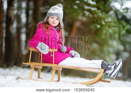 Funny little girl having fun with a sleight in beautiful winter park