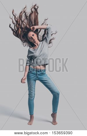 In motion. Full length studio shot of attractive young woman with tousled hair posing against grey background