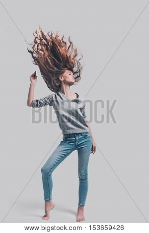 Keep moving! Full length studio shot of attractive young woman with tousled hair posing against grey background
