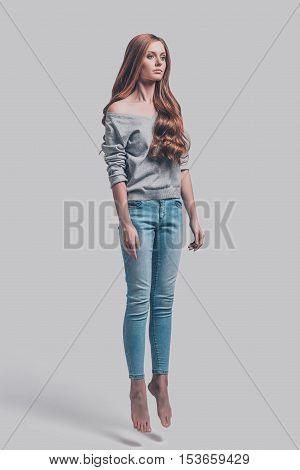 Mid-air motion. Mid-air shot of attractive young woman in casual wear