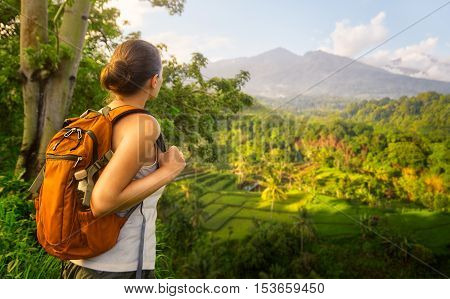 Woman traveler looking at volcano Rinjani island Lombok. Indonesia.Young backpacker traveling along mountains happy female walking discovering world summer vacation concept