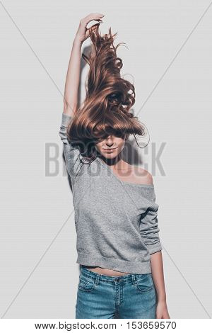 Confident in her healthy hair. Attractive young woman stretching her hair up and while standing against grey background