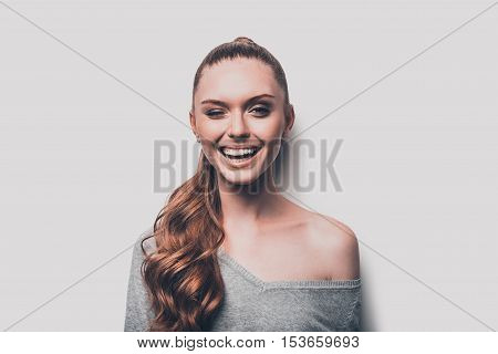 Winking to you. Studio shot of attractive young woman winking to you and smiling while standing against grey background