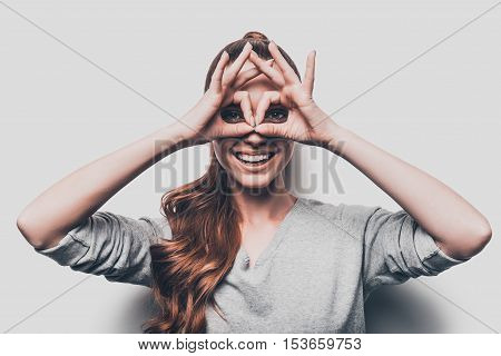 Just for fun. Joyful young woman gesturing eyeglasses near face and smiling while standing against grey background