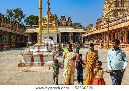 Hampi, India - November 20, 2012: Unidentified Indian tourists visit to the famous landmark. Hindu people walking inside of Shiva Virupaksha Temple located in the ruins of Vijayanagar at Hampi India