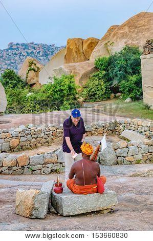 Hampi India - November 19 2012: Monk asking for donation and receiving it from tourist in Hill Malyavanta Raghunatha Temple Hampi Karnataka India.