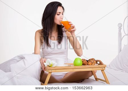 Breakfast in bed. Young woman eating breakfast in bed drinking juice.