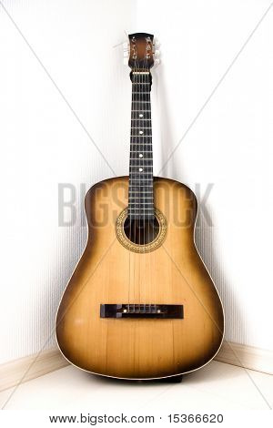 Guitar in a corner of room.