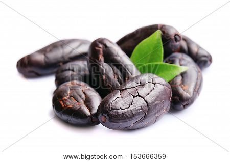 Cocoa beans with leaves close up on white