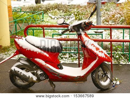 red scooter bike covered with first snow close up photo