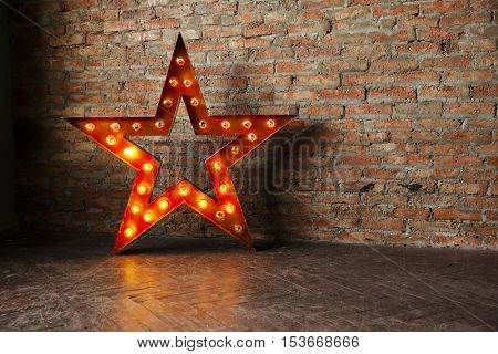 Decorative star with lamps on a background of brick wall. Modern grungy interior