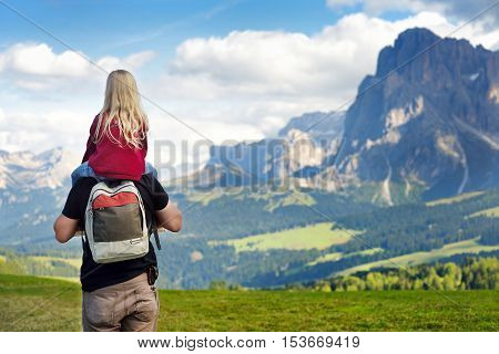 Father and his daughter admiring a view of Seiser Alm the largest high altitude Alpine meadow in Europe with stunning rocky mountains on the background. South Tyrol province of Italy Dolomites.