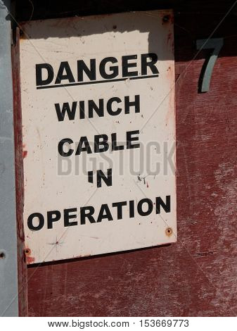 Warning Sign on Winch Cable Building on beach in Village of Beer in Devon UK