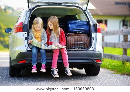 Two Adorable Little Sisters Exploring A Map Before Going On Vacations With Their Parents