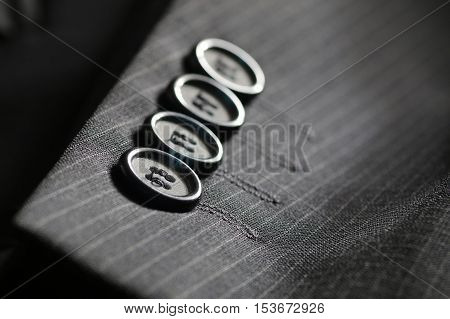 four gray buttons sewn on the sleeve men's suit system