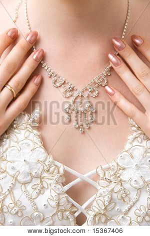 Woman decollete with necklace and hands.