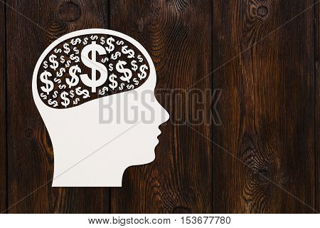 Paper head with many dollar signs inside. Earning money concept. Abstract conceptual image with copyspace. Dark wooden background