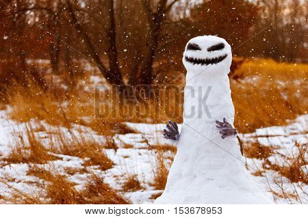 scary snowman as a monster on a background of yellow grass. Halloween