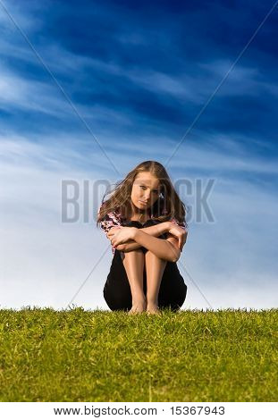 Young woman sitting on a grass.