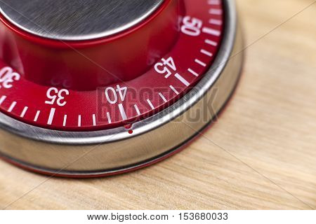 Macro view of a red kitchen egg timer showing 40 minutes on wooden background