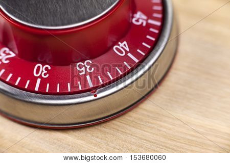 Macro view of a red kitchen egg timer showing 35 minutes on wooden background