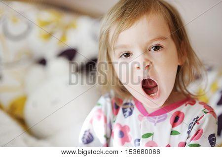 Little Yawning Girl In Pajamas On Sunny Morning