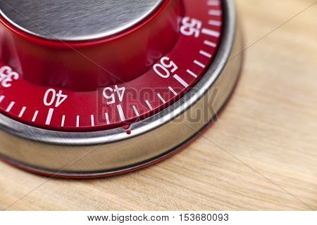 Macro view of a red kitchen egg timer showing 45 minutes on wooden background