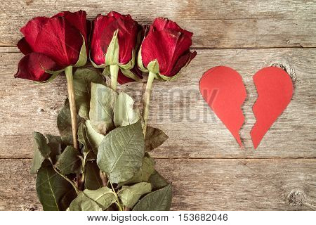 Divorce concept - red broken heart with dry roses on wooden background