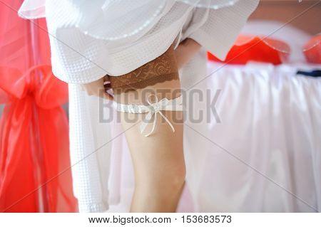 Bride Adjusting White Garter On Her Leg