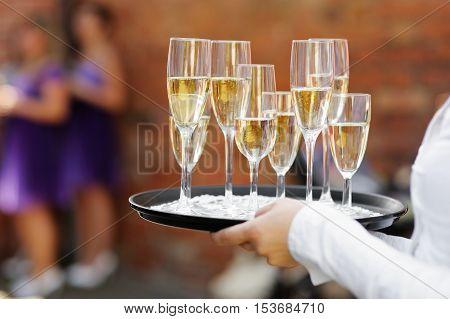 Waiter serving glasses of champagne at festive event