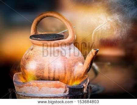 Traditional coffee brew pot withe smoke on blurred background