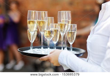 Waiter serving champagne on wedding or another festive event