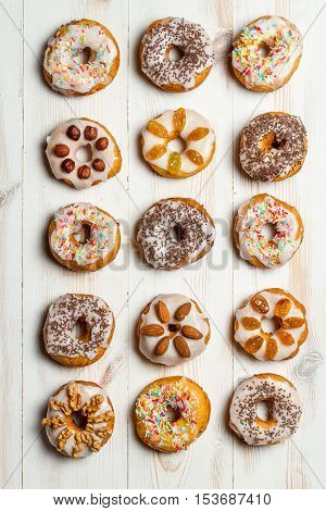 Closeup of large group of variously decorated donuts