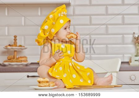 girl the child in a yellow suit of the cooksits on a kitchen table eats croissant