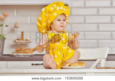 baby girl in a yellow spotty suit of the cooksits on a kitchen table screws up the face holds a wooden kitchen shovel