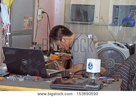 Man Is Repairing Laptop In Small Open Service Room