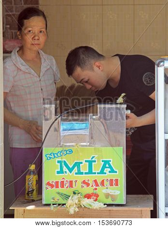Man And Woman Are Checking The Automatic Filling Machine In Vinh, Vietnam