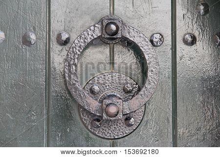 iron doorknocker on a old green wooden door