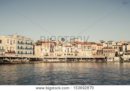 CHANIA, CRETE ISLAND, GREECE - JUNE 26, 2016: View of the old Venetian port of Chania on Crete island, Greece. Tourists relaxing on promenade.