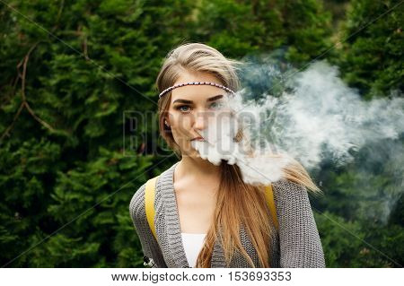 Happy vaping young white blonde girl.Smiling female model smoking fruit flavored e-liquid or e-juice with vaporizer device or e-cig.Modern gadget for smokers