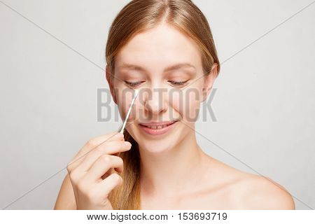 Woman removes makeup from the face with a cotton swab. Happy beautiful young woman cleaning skin by cotton swab.