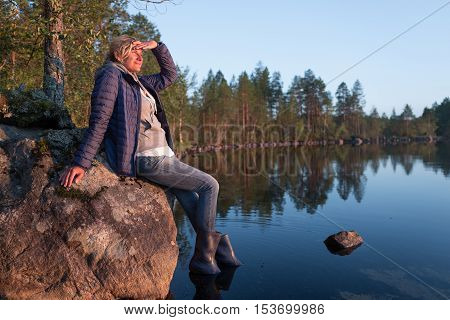 Beautiful tourist woman is sitting on the stone near of the sunset lake and looking into the distance