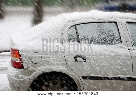 Europe winter snowfall. The car on the parking covered with snow.