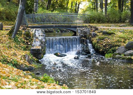 Falls and the bridge through the small river in the park in the fall