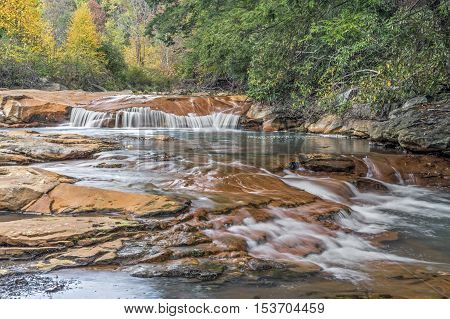 An un-named waterfall spills over red sandstone with autumn foliage surrounding the North Branch of West Virginia's Blackwater River.
