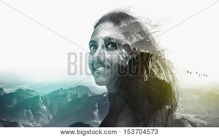 Double exposure portrait of a beautiful attractive woman and rough wild mountain scenery