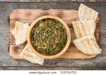 Baba ganoush in bowl and pita bread on wooden table