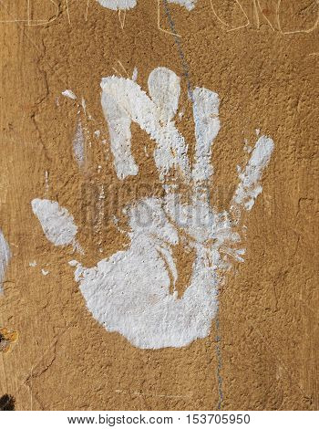 White hand print on a stone wall