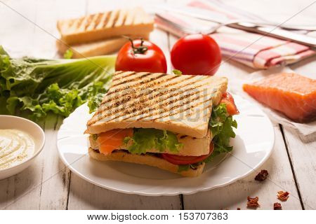 Club sandwich prepared with fish on the wooden surface. Served with tomatoes and sauce. Side view, horizontal orientation