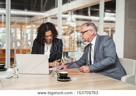 Mature businessman and young work colleague talking together over paperwork and a laptop while sitting at a table in an office boardroom